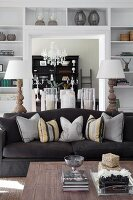 Coffee table, black sofa with arranged scatter cushions, two table lamps and white fitted shelves surrounding doorway in background