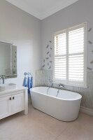 Free-standing bathtub below window with closed interior shutters next to white, rustic washstand