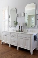 White washstand with twin sinks below two mirrors flanked by sconce lamps