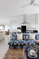 Blue and white patterned sofa and coffee table in open-plan interior with kitchen on background