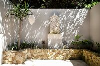 Raised bed with stone surround on sunny patio with tall white wall