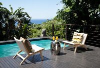 Terrace with integrated pool, outdoor easy chairs and drum-shaped chrome side table