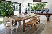 Long wooden dining table and classic chairs next to open folding sliding glass doors with view of garden