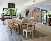 Long wooden dining table and classic chairs on striped rug in open-plan interior; sunken area separated by low wall