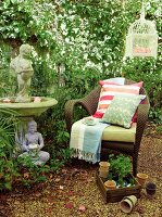 Wicker armchair, classic stone fountain and Buddha figurine next to climber-covered wall in garden