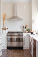Stainless steel gas cooker and extractor hood in modern kitchen