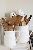 Wooden cooking utensils in white ceramic jugs