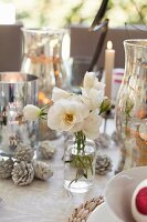 White roses in glass bottle amongst silver candle lanterns and Christmas decorations