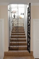 Stairwell with wrought iron gate and sisal carpet