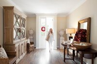 Elegant foyer with glass-fronted dresser, Christmas wreath on table and woman walking in through open front door
