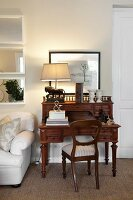 Antique chair and bureau made from dark wood, table lamp with pale lampshade and white sofa