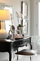 Plexiglas chair at antique, dark-wood dressing table with table lamp with pale lampshade