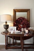 Wooden console table decorated with festive wreath of red leaves, tealight holders and table lamp with pale fabric lampshade