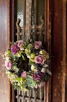 Vintage-style wreath of flowers and succulents on door