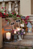 Stone steps festively decorated with lit candles in lanterns and flower arrangements