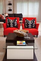 Low coffee table made from various materials in front of bright red armchairs and black and white scatter cushions in modern, elegant interior