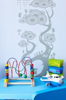 Toys on blue table against wall with stencilled tree motif