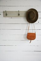 Hat and leather bag hanging from coat rack painted grey on white board wall