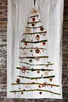 Stylised Christmas tree made from mossy branches with festive decorations hanging on white cloth