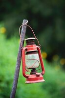 Vintage storm lamp attached to metal rod in garden