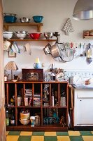 Vintage kitchen with collection of colanders on shelves and hooks and open-fronted, cluttered wooden base cabinet