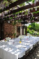 Festively set table below summery, climber-covered pergola outside country house
