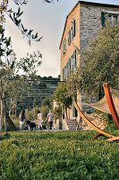 Family on terrace of Italian farmhouse in Ligurian mountain landscape
