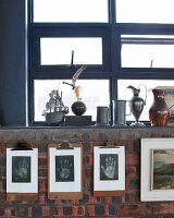 Collection of pewter jugs on sill of blue window above artistic hand prints on clipboards on brick wall