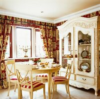 A round dining table laid with crockery under a window in an elegant country house-style kitchen with red-patterned wallpaper and a grand display cabinet
