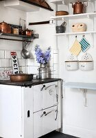 Nostalgic, vintage kitchen with wall-mounted shelf, cooker and copper pots and pans