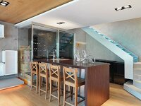 Wine bottles in glass rack and wooden stools at bar counter; Scottsdale; USA