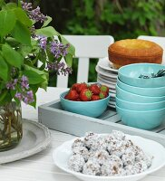 Chocolate truffles on white dish, tray of blue bowls, strawberries and cake on garden table