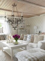 Ottoman and sofa around white coffee table below wrought iron candle chandelier hanging from wooden ceiling in rustic living room
