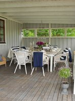 Set table and white wicker chairs on wooden floor of loggia