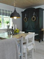 Simple dining table and white kitchen chairs below vintage pendant lamp; farmhouse cupboard painted black with wreaths on doors