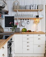 White, country-house-style kitchen; table lamp on kitchen counter below shelves of glasses and mugs on wooden wall