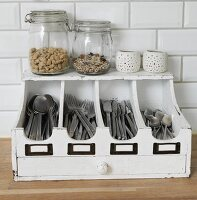 Storage jars and tealight holders on old, white-painted cutlery tray with drawer