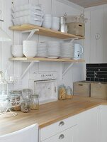 Corner of kitchen with crockery on bracket shelves on white wooden wall and storage jars on worksurface