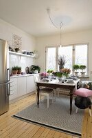 Scandinavian kitchen with vintage dining table and stainless steel fridge