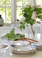 Flea market crockery and glasses, rhubarb and lilac on white dining table