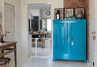Blue-painted farmhouse cupboard against brick wall next to baby gate in kitchen doorway