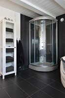 Modern shower cabinet and towels in vintage, glass-fronted cabinet in black and white bathroom in Scandinavian wooden house