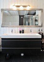 Eclectic black and white bathroom with modern washstand and antique mirror on wall with Scandinavian wood panelling