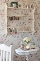Vase of flowers on side table below shelving on wall with floral wallpaper