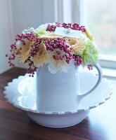 White ceramic jug of flowers and berries in bowl