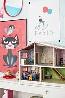 Colourful children's posters on wall and doll's house on cabinet