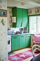Kitchen cabinets with green doors and rug with star motif on wooden floor