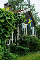 Rustic wooden house with Swedish flag on terrace