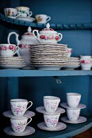 Floral crockery in blue cabinet