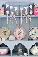 Silver cutlery and antique decorative plates on wooden shelves
